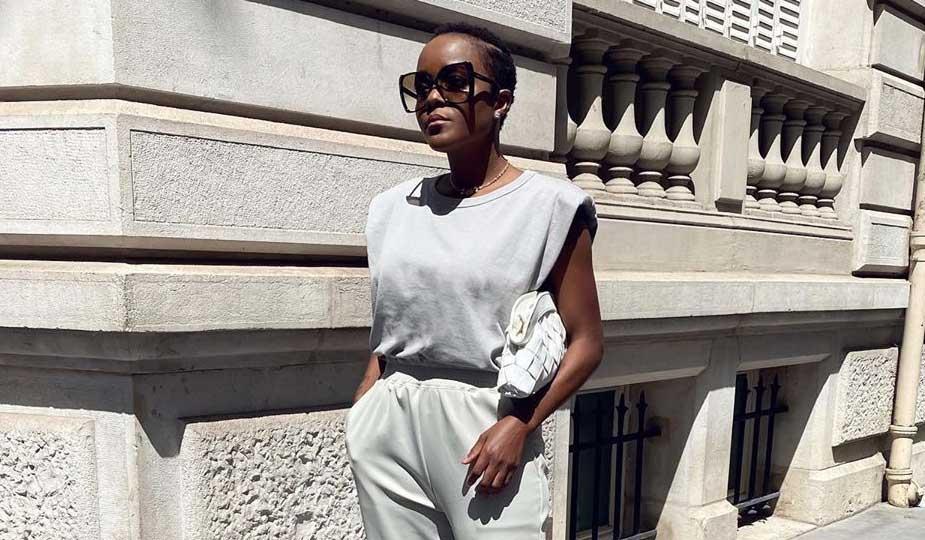 Mulher negra jovem vestindo camiseta muscle tee clara sob sol